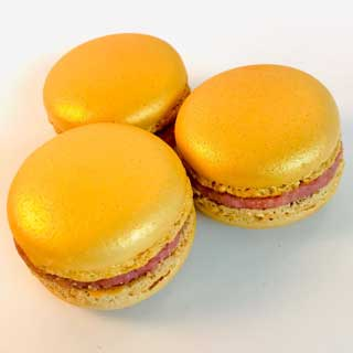 gouden macaron met een ganache van witte chocolade en aardbei